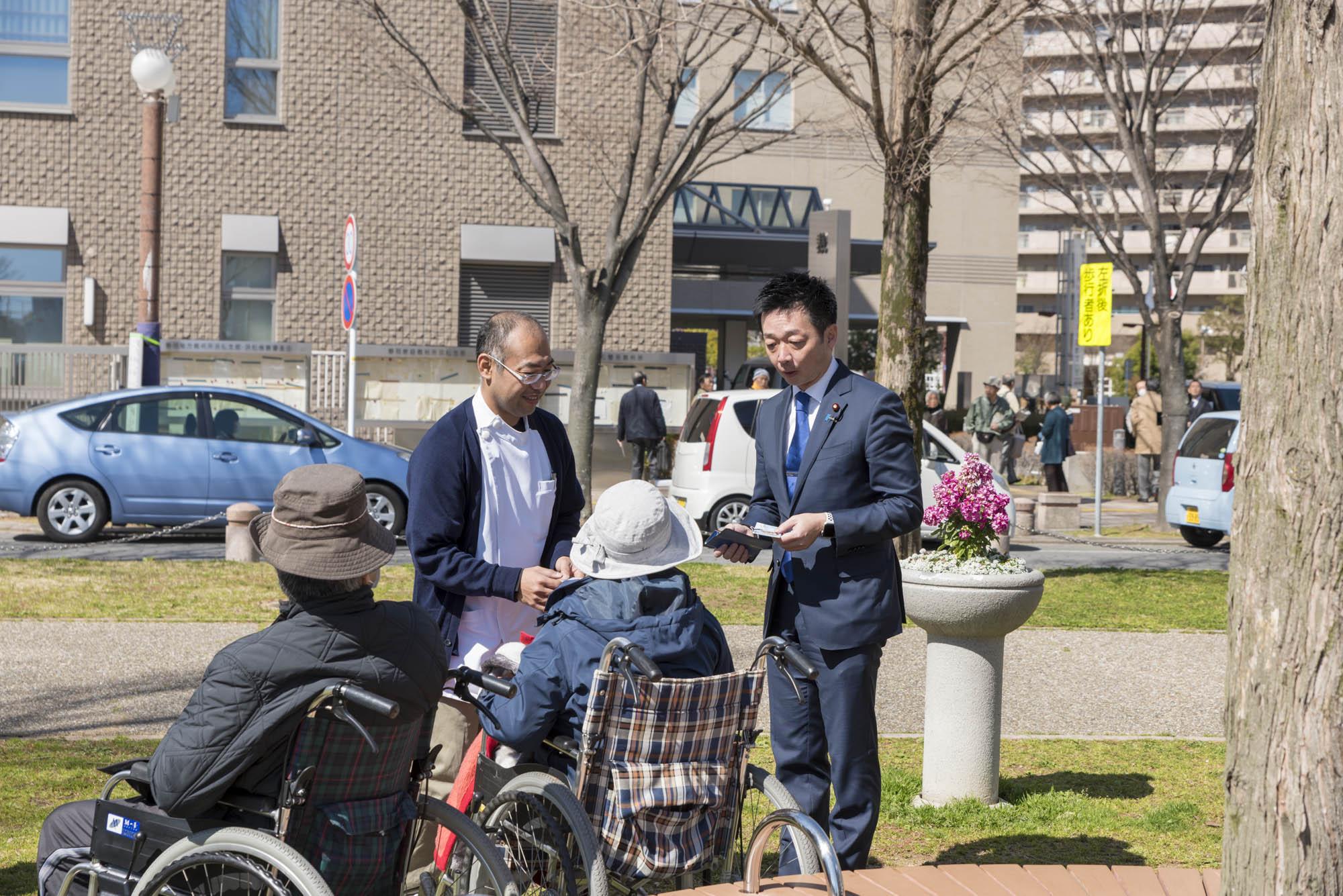 高齢者とコミュニケーションをとる源馬謙太郎